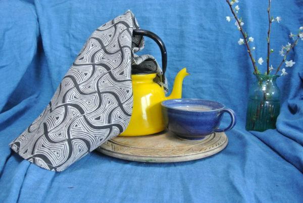 Tea towel in charcoal St Peter print, on display